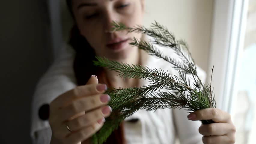 Branch of the Christmas tree in the hands of a middle-aged woman | Shutterstock HD Video #1020700297