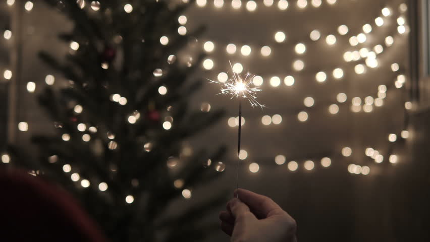 Sparkler in hand with celebrate Christmas lights background. | Shutterstock HD Video #1020703657