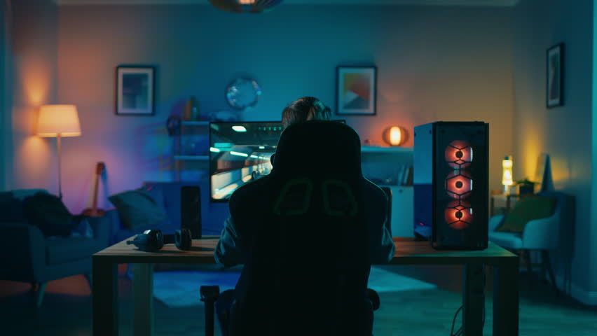 Back Shot of a Gamer Playing and Winning in First-Person Shooter Online Video Game on His Powerful Personal Computer. Room and PC have Colorful Neon Led Lights. Cozy Evening at Home. | Shutterstock HD Video #1020758407