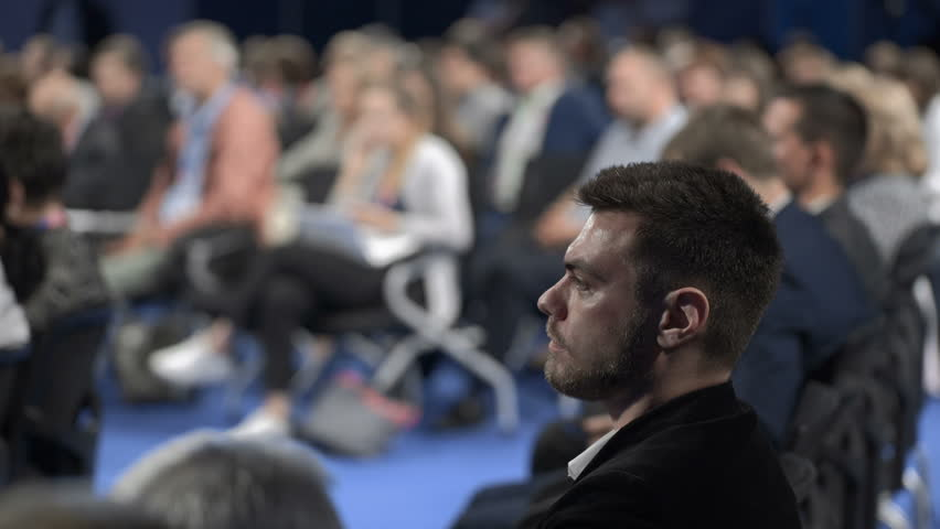 Crowded education trading forum. View of speaker speech in modern large place. Expert businessperson or caucasian confident listener on row of chair seats. Occupation for professional corporation idea | Shutterstock HD Video #1020788587