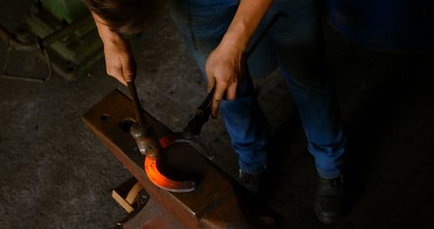 Overhead of young female metalsmith with short hair molding horseshoe in factory. She hit the glowing warm horseshoe with a hammer.