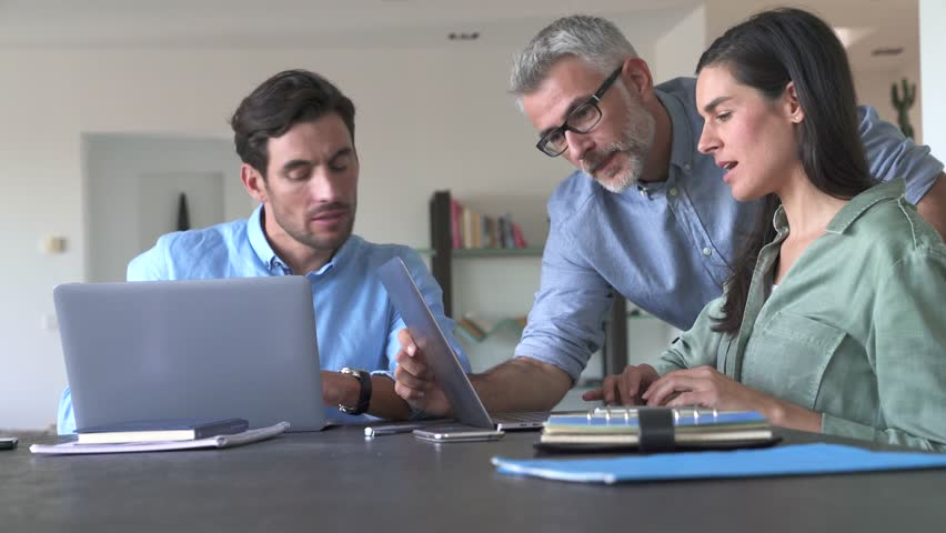 Young colleagues with older boss working with computers                               | Shutterstock HD Video #1020858097