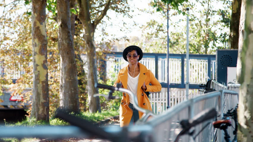 Fashionable young black woman wearing a hat, sunglasses, blue jeans and a yellow pea coat walking towards camera along a treelined street on a sunny day listening to music with earphones, selective fo   Shutterstock HD Video #1020861397