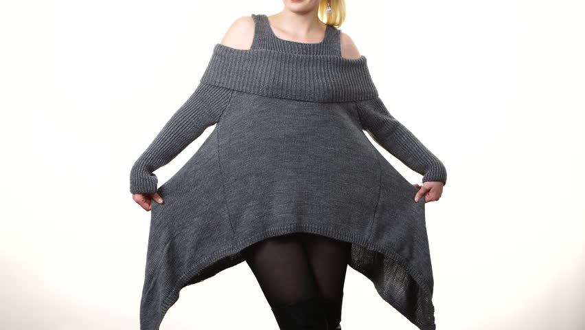 Happy blonde woman wearing fashionable grey long sleeve cold shoulder jumper woolen sweater, attractive model presenting clothing on white. Fashion concept   Shutterstock HD Video #1020865777