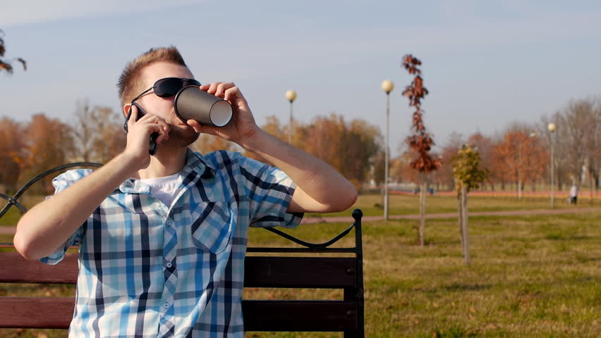 Young stylish and trendy man in black glasses sits on a bench drinking coffee and talking on the phone, close-up, copy space, slow motion, fashionable   Shutterstock HD Video #1020878227