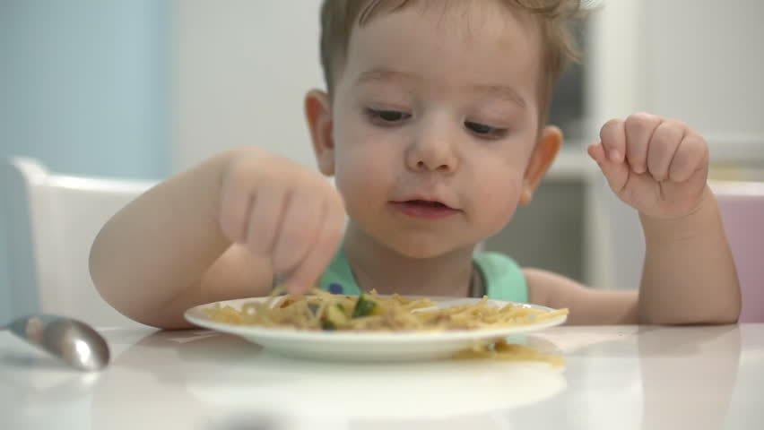 Small child is sitting at a table in a bib and eat his own spaghetti, the baby eats willingly. | Shutterstock HD Video #1020902047