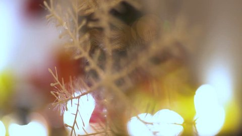 Decorative snowflake hanging from ceiling in the room, close up, happy new year, best wishes, blinking lights on ornamental Christmas tree in blurred background, winter symbol, shallow depth of field.