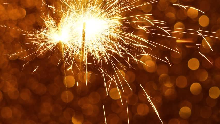 Sparkler burning against Golden Christmas or New Year festive background | Shutterstock HD Video #1020921217