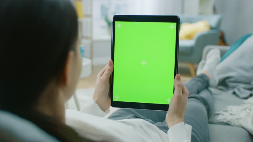Young Woman at Home Resting on a Couch Using with Green Mock-up Screen Tablet Computer in Vertical Portrait Mode. Woman Using Tablet Device, Browsing Internet, Watching Content, Videos. | Shutterstock HD Video #1020934087