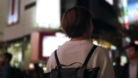Medium shot on 4k RED camera on a gimbal. Content Japanese woman walking through a busy intersection in Shibuya with soft dark, natural lighting.