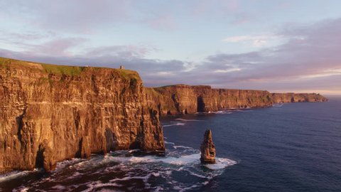 Aerial drone footage of the beautiful Cliffs of Moher off the west coast of Ireland. Waves crashing against the foot of the cliffs located on the Wild Atlantic Way. Scenic view of sea and mountain