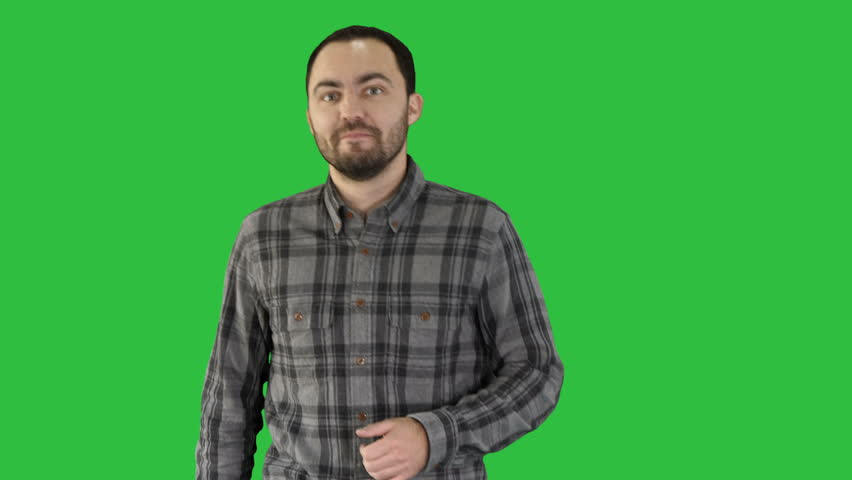 Talking young man explaining something and pointing to the side on a Green Screen, Chroma Key.