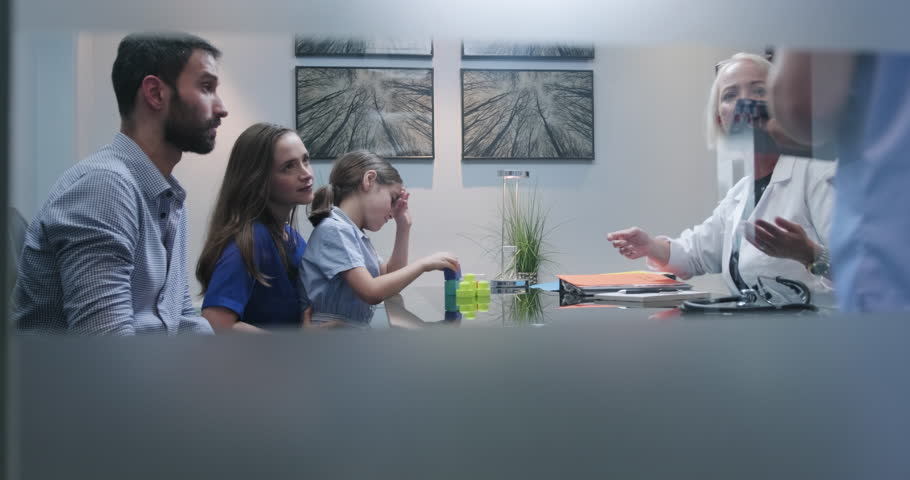 Slow motion shot of a doctor or specialist having conversation in clinic with parents about their autistic girls health. Doctor in hospital show little girl with aspergers lab test results to parents   Shutterstock HD Video #1020966457