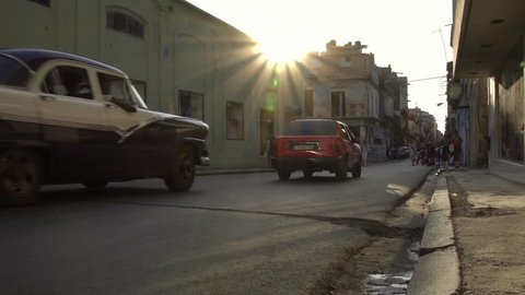 HAVANA, CUBA - Oct 18, 2018: golden hour sun, classic American 1950's Vintage cars drive on old alley street. La Habana Vieja Old Havana is iconic popular tourist destination travel.