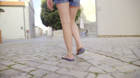a64d4f5ceb49 ... woman wearing flip-flops is walking to her balcony in the city.  Tracking person walking through old city closeup on legs. Camera on gimbal  stabilizer ...