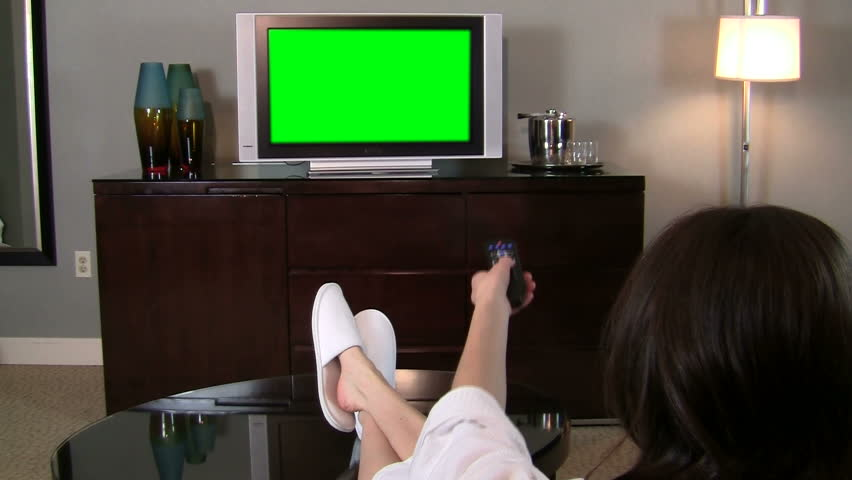 Woman flips channels on green screened TV with remote - HD