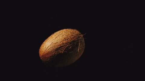 SLOW MOTION: Coconut flies up and falls down on a black background