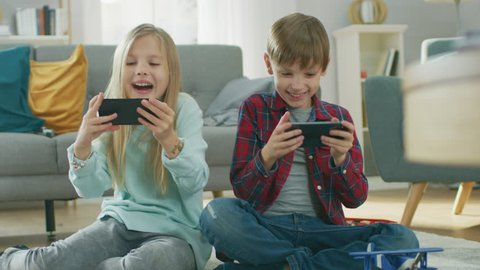 At Home Sitting on a Carpet: Cute Little Girl and Sweet Boy Playing in Competitive Video Game on two Smartphones, Holding them in Horizontal Landscape Mode. Close-up Portrait Camera Shot.