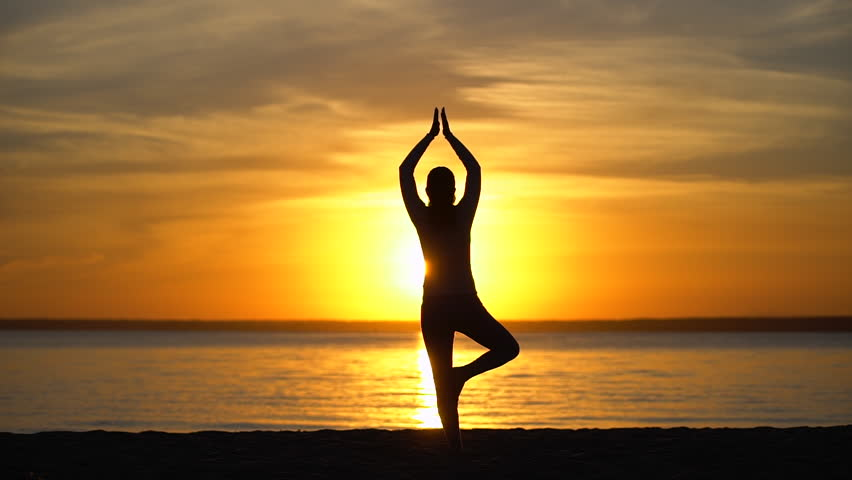Silhouette sporty yoga woman doing tree yoga pose at sunset in nature outdoors. yoga poses, girl with open raised arms practicing yoga in sea water beach. Female working out training meditation, sun