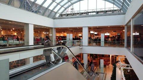 OXFORD STREET, LONDON - DECEMBER 19, 2018: Customers doing their Christmas shopping ride escalators between floors inside Debenhams department store on Oxford Street in London, UK.