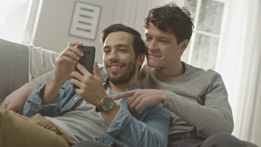 Cute Male Gay Couple Spend Time at Home. They are Lying Down on a Sofa and Use a Smartphone. They Browse Online. Partner's Hand is Around His Lover. They Smile and Laugh. Room Has Modern Interior.