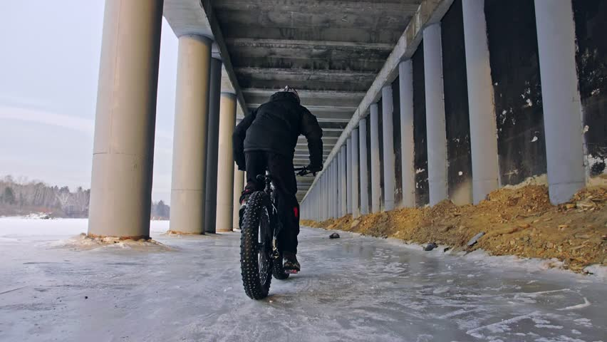 Professional extreme sportsman biker riding fat bike in outdoors. Cyclist ride in winter on snow ice under bridge. Man do trick on mountain bicycle with big tire in helmet glasses. Slow motion 180fps. | Shutterstock HD Video #1021269127