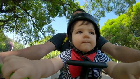 Father with baby riding a bicycle in the park. Ibirapuera park in Sao Paulo city. 4K 60fps.