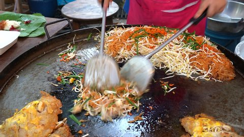 People cooking traditional asian Thailand food Pad Thai in outdoor market, Asia, Thailand