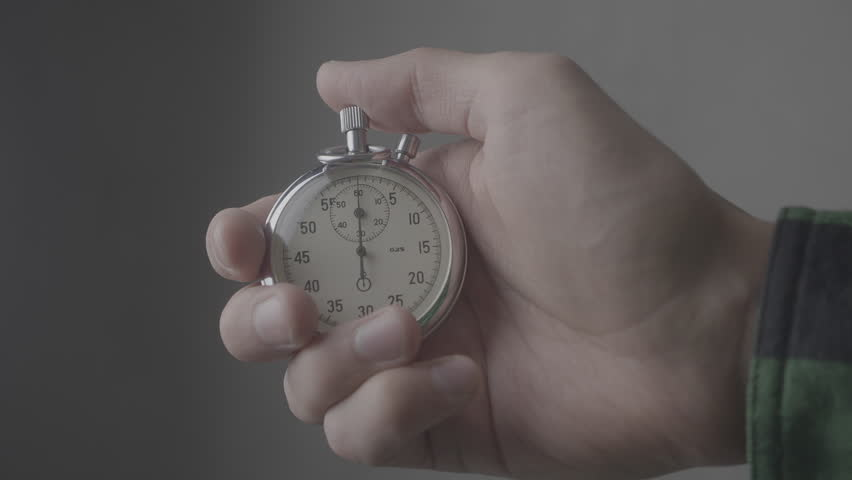 Man's Hand starting up a Stopwatch at gray background 4K, 10 BIT, 4:2:2 | Shutterstock HD Video #1021289167