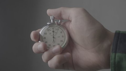 Man's Hand starting up a Stopwatch at gray background 4K, 10 BIT, 4:2:2
