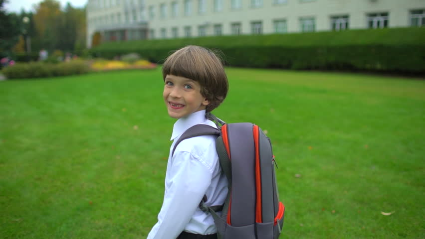 Little boy schoolboy student with backpack going to school outdoors. First-grade student, primary school, first grader, first class 1 september school boy child schoolchild day of knowledge Back view | Shutterstock HD Video #1021300687