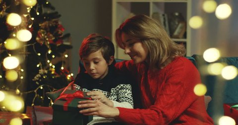 Caucasian beautiful mother and her son sitting at the Christmas tree and opening a present box with surprised and excited faces.