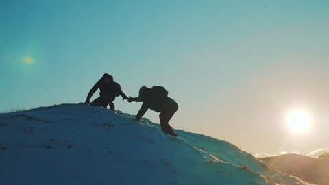 teamwork business travel concept. two hikers tourists climbers climb to the top of the mountain. overcoming hardships the path to victory, teamwork, important points in lifestyle running your business