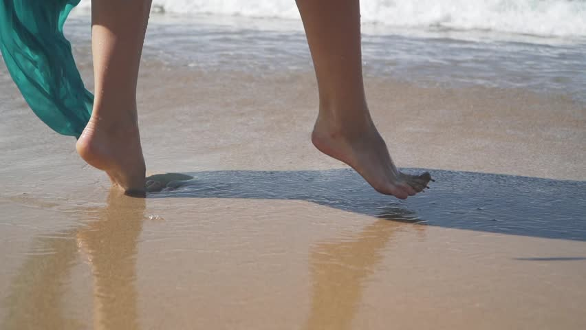 Female bare feet walking on the wet sand on the beach. Slow motion | Shutterstock HD Video #1021322377