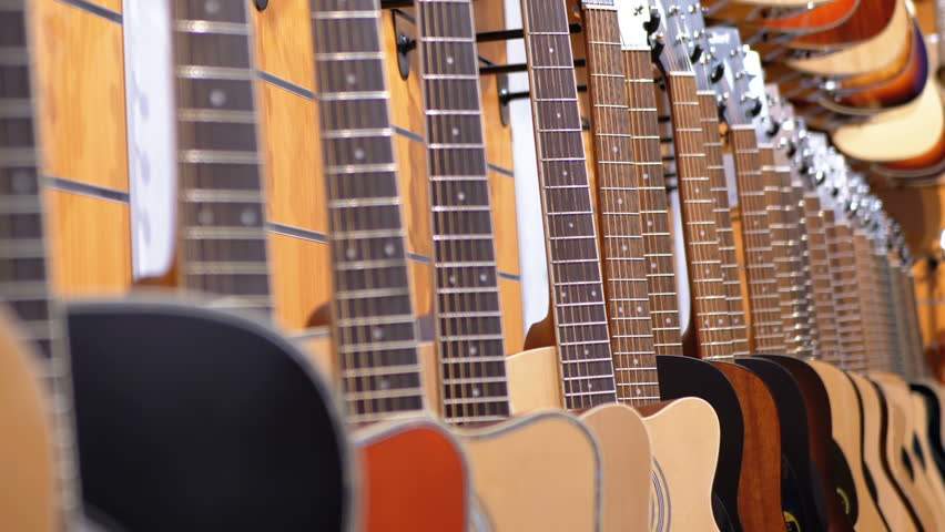 Lot of Acoustic Guitars Hanging in a Music Store. A number of different multi color classic guitars are sold in the store. Shop musical instruments. | Shutterstock HD Video #1021336177