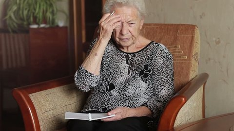 Old man's memory loss. An old woman trying to remember something and write in a notebook