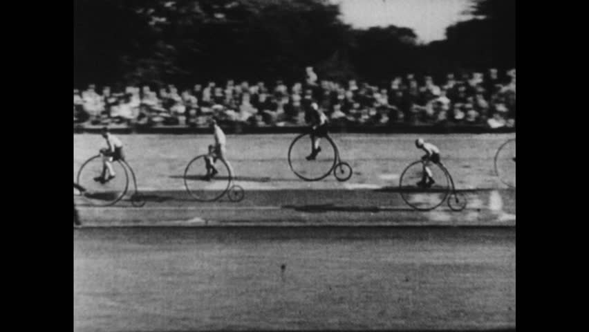 1940s: UNITED STATES: man rides penny farthing bike. Penny farthing bike race. Crowd cheer cyclists.