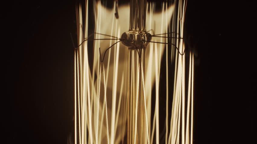 Edison light bulb flickering in the Dark. Vintage filament Edison light bulb. Close up   Shutterstock HD Video #1021392127