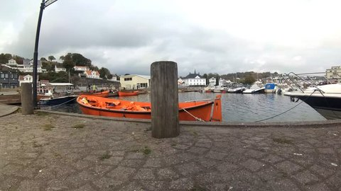 Empty lifeboat in the fall in Grimstad, Norway, waiting for students to board for a field trip to an offshore island. Gray and cloudy,