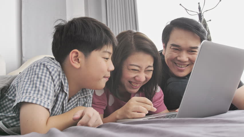 Happy family Father mother and son watching on laptop computer and having fun, Slow motion 4K  asian family rest on bed with laptop computer | Shutterstock HD Video #1021435987