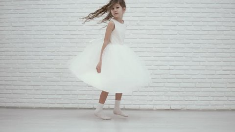 beautiful girl dancing in a chic white dress. The girl is spinning, her dress is developing from the movement. Beautiful video of a little bridesmaid at a wedding
