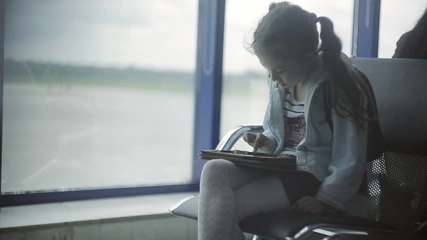 A little girl at the airport at the window uses a tablet | Shutterstock HD Video #1021489447