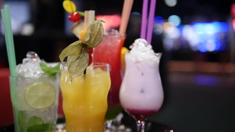 Close up of beverages. Several various cocktails and colorful drinks in a nightclub or pub on a blurred background with lights
