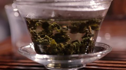 Process of brewing and unfolding fermented oolong tea leaves in glass gaiwan or tea-bowl, macro footage