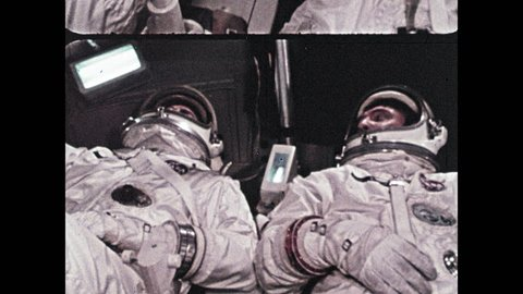 1960s: Astronauts inside spaceship. Crane moves surface module craft.