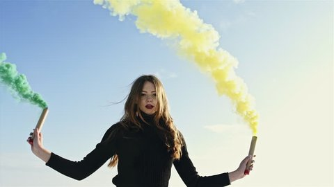 Woman makes emergency flare signal. Hipster girl with smoke bomb