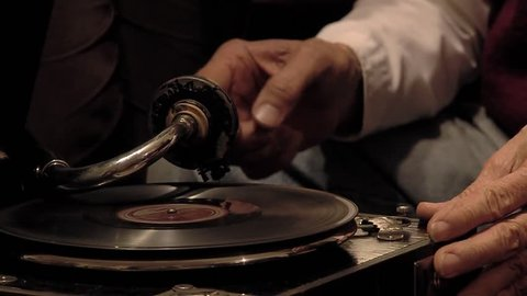 Male Hands Putting Needle on an Old Vinyl Record.