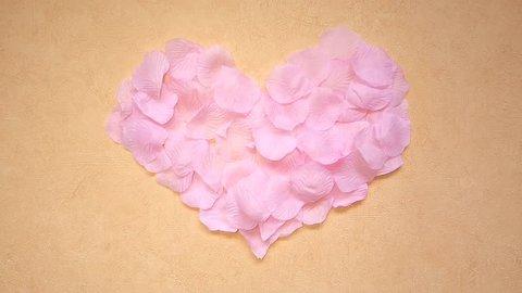 Pink rose petals form a heart shape. A gust of wind blows the petals away.