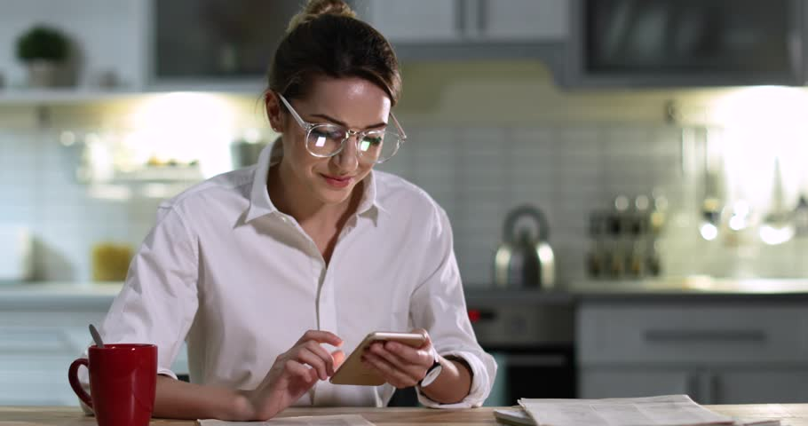 Beautiful young woman using smartphone at table in kitchen  | Shutterstock HD Video #1021660777
