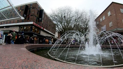 Coventry, West Midlands, UK - December 31, 2018: View through a fountain of people shopping on the pedestrian area looking towards Smithford Way in Coventry city centre